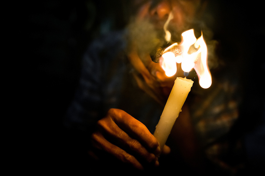 A Colombian urban shaman (brujo) lights up three cigars to devine the future from burn tobacco leaves in his house in Cali, Colombia, 17 April 2013. Although the original spiritual tradition, kept by the indigenous shamen in Americas for centuries, has been systematically repressed by the Catholic Church, nowadays, more and more people from the urban areas of Latin America discover their roots and consult their everyday problems with esoteric practitioners, healers and shamen. Traditional indigenous rituals (reading of tobacco - interpretation of signs shown by burn tobacco leaves) have merged with European concepts (divination using playing cards) and animistic religious beliefs (worshipping the spirits) brought to Americas by the African slaves, keeping the spirituality in modern Latin American society alive.