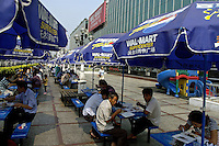 Exterior of US Wal Mart 'Supercenter' in Shenzhen, China, with people eating food bought at its lunch counters, The umbrellas are also decorated with advertising for Pepsi..01 Nov 2004