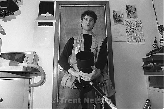 Trent Nelson in the Daily Herald darkroom with equipment and vest, posing.<br />