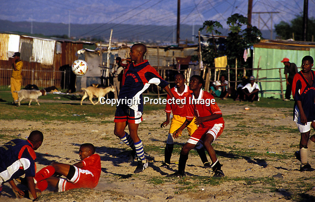 dippchi00283 Children.  Boys playing soccer on July 23, 2001 in Site B Khayelitsha, a township about 35 kilometers outside Cape Town, South Africa. Khayelitsha is one of the poorest and fastest growing townships in South Africa. Goats and shacks in the back.©Per-Anders Pettersson/ iAfrika Photos.