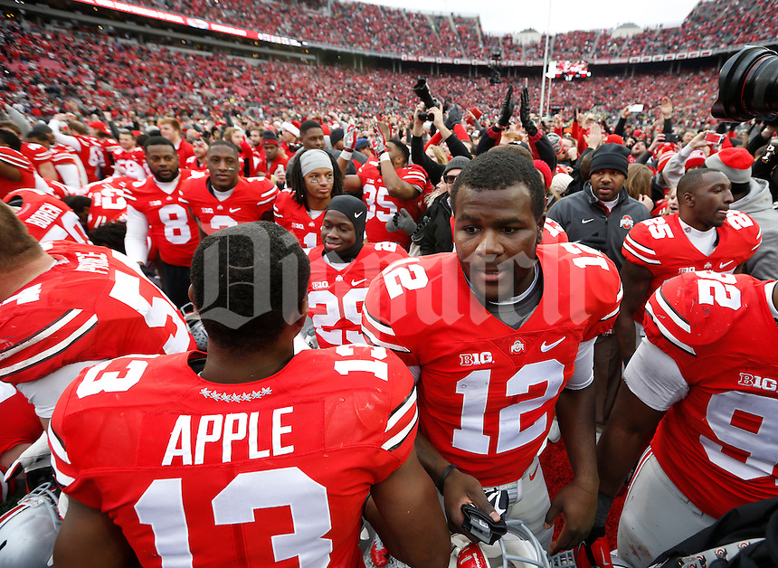 Ohio State Buckeyes quarterback Cardale Jones (12) walks off the field after singing Carmen Ohio with teammates following the NCAA football game against the Michigan Wolverines at Ohio Stadium on Nov. 29, 2014. The Buckeyes won 42-28. (Adam Cairns / The Columbus Dispatch)