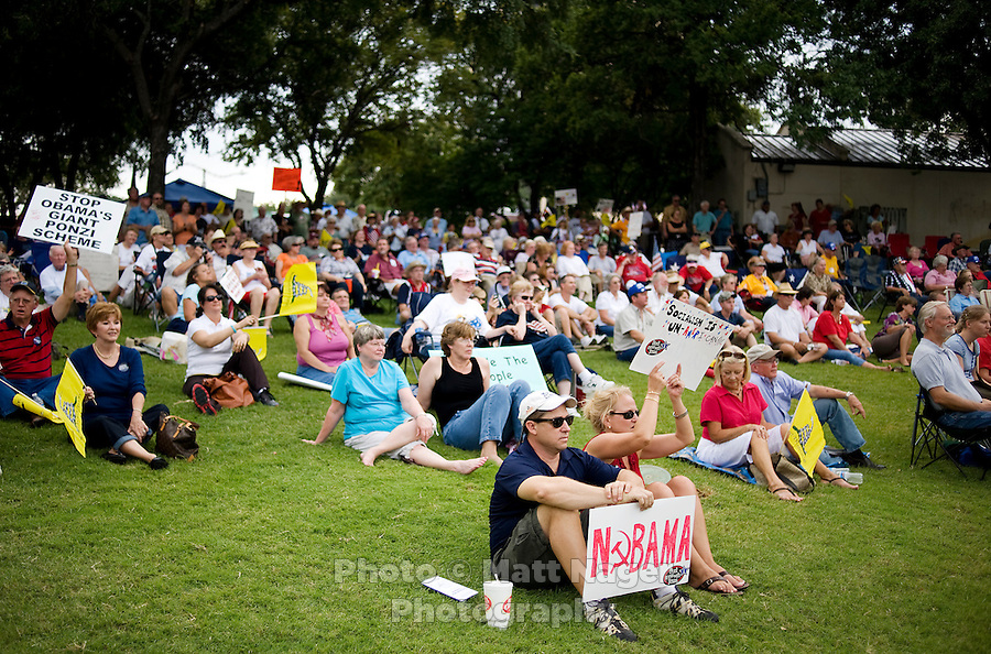 Supporters of the Tea Party Express, a traveling national bus tour of people against higher government spending, higher taxes, and President Obama's push to reform health care, hold signs during a rally at Indian Spring Park in Waco, Texas, Thursday, September 3, 2009. The Tea Party Express is heading to Washington, DC where it will hold a final rally and march...PHOTOS/ MATT NAGER
