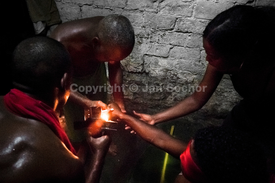A Cuban man, the Palo religion priest, draws a magical symbol on the young man's skin during a secret initiation ritual of the Palo Monte religion in Santiago de Cuba, Cuba, August 1, 2009. The Palo religion (Las Reglas de Congo) belongs to the group of syncretic religions which developed in Cuba amongst the black slaves, originally brought from Congo during the colonial period. Palo, having its roots in spiritual concepts of the indigenous people in Africa, worships the spirits and natural powers but can often give them faces and names known from the Christian dogma. Although there have been strong religious restrictions during the decades of the Cuban Revolution, the majority of Cubans still consult their problems with practitioners of some Afro Cuban religion.