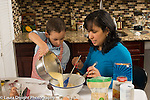 3 year old boy in kitchen at home with mother learning to cook baking, pouring batter into bowl