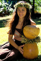 Portrait of a part Hawaiian woman in a haku lei sitting with an ipu heke (gourd) hula implement
