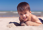 Portrait of a cute happy child playing in the sand on the beach. Lake Huron, Ontario, Canada.