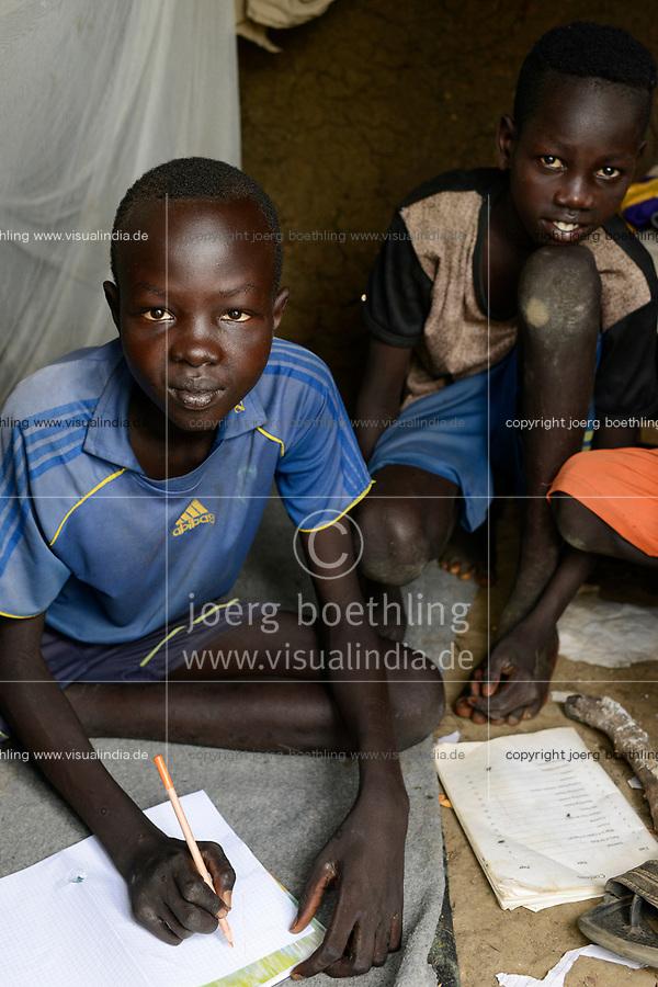 ETHIOPIA, Gambela, region Itang, Nuer village Pilual, boy Bhan 12 years old / AETHIOPIEN, Gambela, Region Itang, Dorf Pilual der Ethnie NUER, Hof von Herr Mun Kunen und Frau Neelam , sie sind vor dem Buergerkrieg aus dem Suedudan gefluechtet, Junge Bhan 12 Jahre macht Hausaufgaben