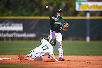 Dartmouth Big Green shortstop Nate Ostmo (19) throws to first base as Max Schuemann (17) slides into second base during a game against the Eastern Michigan Eagles on February 25, 2017 at North Charlotte Regional Park in Port Charlotte, Florida.  Dartmouth defeated Eastern Michigan 8-4.  (Mike Janes/Four Seam Images)