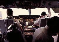 Pilot, copilot and engineer at work in cockpit during flight; instrument panels. Canada Air route California to Toronto.