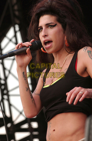 AMY WINEHOUSE.2nd Annual Virgin Festival By Virgin Mobile - Day One held at Pimilco Race Course, Baltimore, Maryland, USA,.04 August 2007..half length singing live on stage on-stage gig concert music black vest top tummy stomach midriff belt microphone beehive tattoos .CAP/ADM/DS.©Devin Simmons/AdMedia/Capital Pictures.