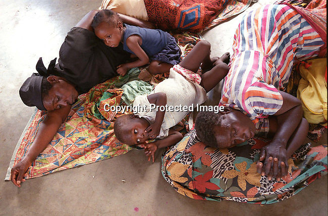 A family resting in Chaquelani, a transit camp for flood victims in Mozambique; mother with children; people lyimng on the floor; floods; Mozambique..©Per-Anders Pettersson/iAfrika Photos