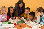 Female teacher working with students science activity 4th grade students ages 9-10
