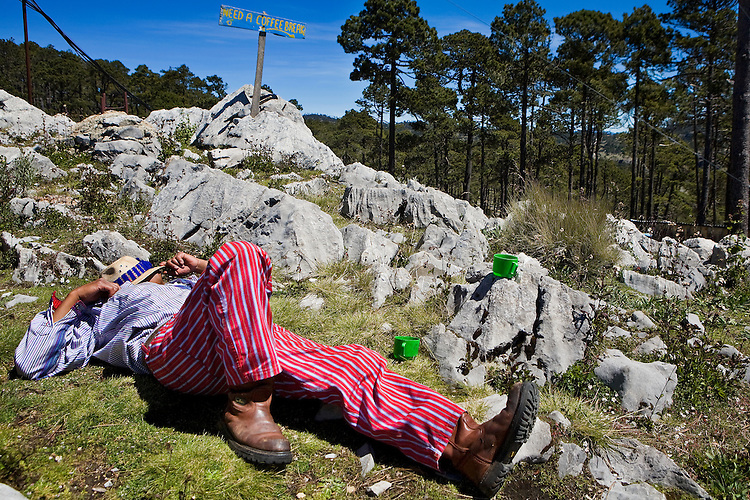 Guatemalan man wearing clothes from Todos Santos takes a nap on top of La Torre, the highest non volcanic point in Central America, Western Highlands, near Todos Santos Cuchumatan.