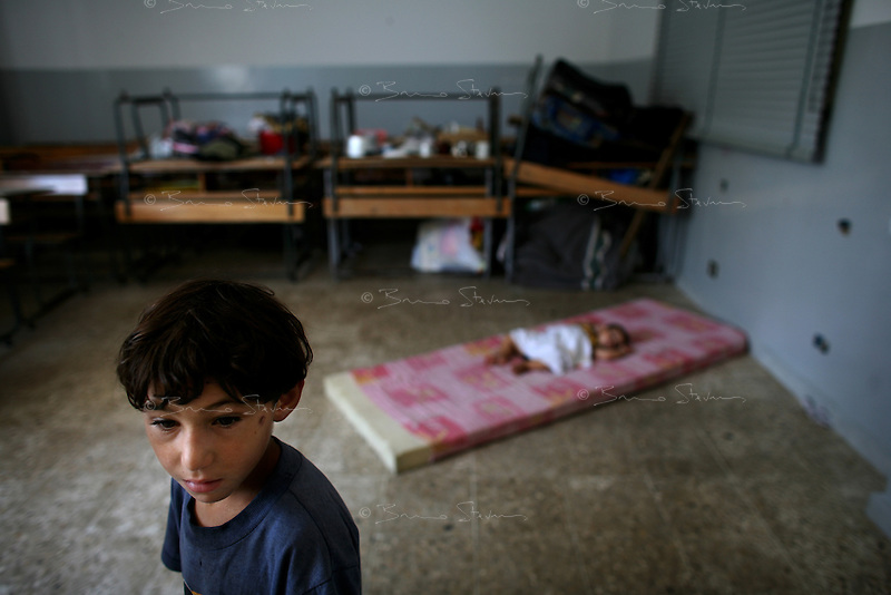 Tyr, Lebanon, Aug 4 2006.Adi Mansoori, 8, with his little brother Mahdi, 1. Hajj Mariama school (St. Mary), Hundreds of refugees from Shatiyeh, a nearby village heavily bombarded by the Israeli arrived only with the clothes they were wearing as they fleeed their destroyed homes in a hurry.