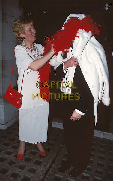CHRISTINE & NEIL HAMILTON..Ref: 11489..celeb couple, funny, feather boa, red shoes, red bag, red purse..www.capitalpictures.com..sales@capitalpictures.com..©Capital Pictures..full length, full-length