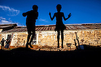 I photographed these girls skipping at an abandoned goldmine hostel that is home to them and many poor families on the outskirts of Johannesburg, South Africa. In the previous few weeks before this photograph was taken, the area had been robbed of all its cable (stolen for its copper) so no one had electricity anymore. Ironically, the girls were using the rubber part from stolen cable to skip with! Despite very difficult circumstances, the kids were having so much fun.