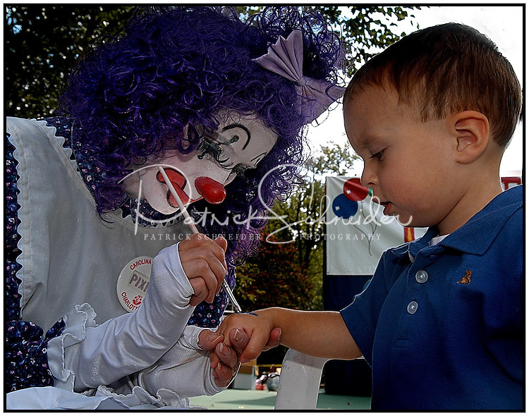 A clown paints on the hand of a young boy at a festival. Boy is model released, but clown is not.