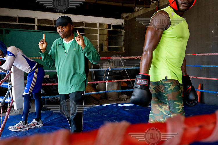 Trainer James Ike offers stern words of advice to Angel Harrison (left) and Yomi Shokunbi (right) between rounds of sparring at the Hillbrow Boxing Club. Both boxers are aspiring professionals, hoping to qualify for their boxing licences in a few weeks time.<br />  Hillbrow, in downtown Johannesburg, is the city's most notorious neighbourhood. It is overcrowded, ridden with illegal squats and suffers from high levels of crime much of which is related the thriving illicit drug trade. Against this backdrop, George Khosi's story is not atypical. A childhood spent on the streets, where he survived by committing petty crime and hustling, led to imprisonment at the age of 16. Because he was big and looked older than his age this incarceration was in an adult institution. Here he began to fight since, as he says 'they wanted to make me a woman and I didn't want to be a woman.' When he got out, he took up boxing in earnest.&nbsp;His prospects as a professional boxer looked bright until he was shot and left for dead during a burglary. He lost his right eye and now walks with a limp. His boxing career seemed over but George picked up his gloves again, this time to teach Hillbrow's youngsters. His gym became a place of hope and discipline for local youth, keeping them of the streets and even producing some national champions.