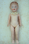 Vintage female doll with face slightly freckled from ageing and wearing three rows of pearls  lying naked on antique paper