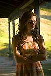 Young woman seen through screen door, standing on porch