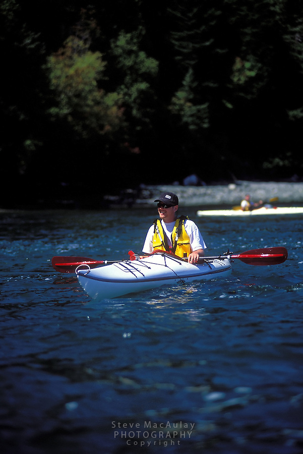 Smiling male sea kayaker with ball cap , yellow PFD and red paddle resting,  Cypress Island, San Juan Islands, Washington
