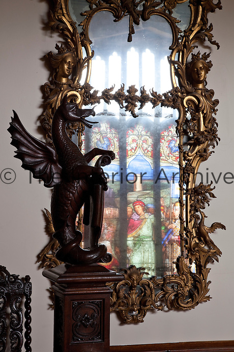 A stained glass window is reflected in an eighteenth century Irish giltwood pier glass on the staircase landing