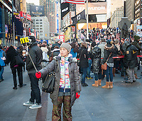 Tourists in Times Square in New York use their selfie sticks to take selfies of themselves and their companions on Friday, January 2, 2015. The goofy looking accessory was extremely popular this holiday season with many stores having problems keeping them in stock. Estimates are that 100,000 have been sold in the U.S. in December alone and Time magazine christened them the one of the best inventions of the year. (© Richard B. Levine)