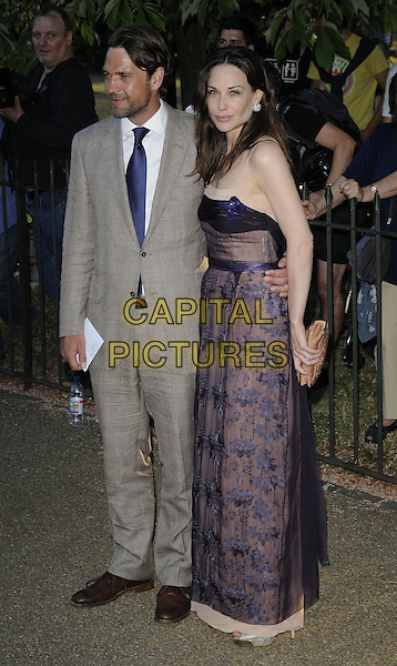 DOUGRAY SCOT & CLAIRE FORLANI .At the Serpentine Gallery Summer Party, Serpentine Gallery, Hyde Park, London, England, UK, July 8th 2010..full length beige grey gray suit tie black print dress navy blue brown married husband wife couple clare brown shoes checked plaid check patterned embroidered clutch bag .CAP/CAN.©Can Nguyen/Capital Pictures.