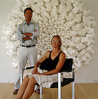 Architects Peter Franck and Kathleen Triem in front of a large sculpture that is mounted on the wall of their living room