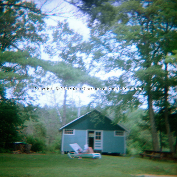 Sunbather in lawn chair in front of blue building surrounded by trees