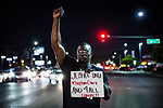 SACRAMENTO, CALIFORNIA - MARCH 31, 2018: Tyvonne Joseph protests in the street during a candlelight vigil for Stephon Clark in South Sacramento. In the days since Stephon Clark, 22, was fatally shot by officers investigating a vandalism complaint in his south Sacramento neighborhood, protesters have stormed City Hall and taken to the streets in anger. CREDIT: Max Whittaker for The New York Times