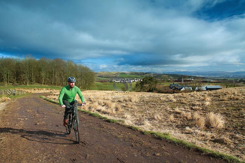 A cyclist cycling around Neilston Pad, Neilston, East Renfrewshire
