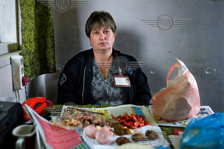 Security guard, 45 year old Maria Placinta,  sits with her lunch in a security booth at the Petrila mine.