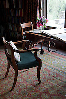 An armchair with a green leather seat is drawn up to a desk in the library