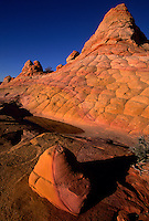 Crossbeds of Navajo sandstone paint the Coyote Buttes in hues created by the precipitation of oxides. From a 3,000-foot-high escarpment to a canyon 2,500 feet deep, Vermilion Cliffs National Monument encloses a remote and unspoiled, 294,000-acre geologic treasure on the border of Arizona and Utah north of the Grand Canyon.