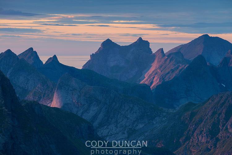 Last light shines across rugged mountain landscape of Moskenesøy, Lofoten Islands, Norway