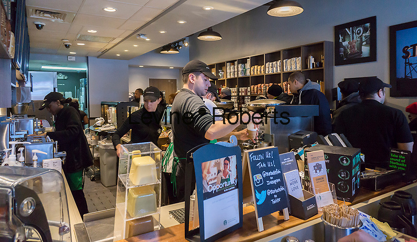 A barista prepares a coffee in a busy Starbucks in Queens in New York on Saturday, February 13, 2016.  (© Richard B. Levine)