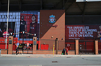 May 4th 2020, Liverpool, United Kingdom; Anfield stadium during the suspension of the Premier League due to the Covid-19 virus pandemic; passers by outside the locked and deserted entrance to the Kop end of the stadium