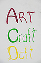 """Sign painted on house exterior, reading """"Art. Craft. Daft"""" in red, green and yellow paint, Reykjavik, Iceland."""