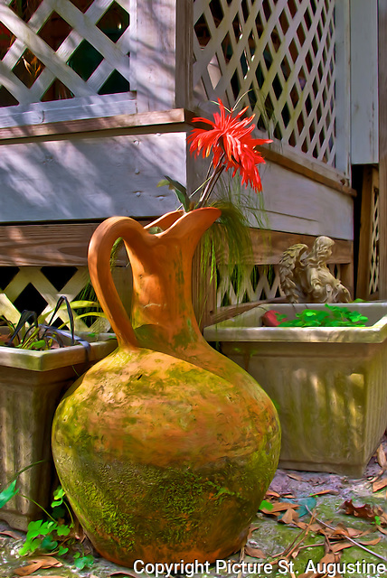 Old pottery water vessel with orange flower next to a lattice work porch in St. Augustine, Florida