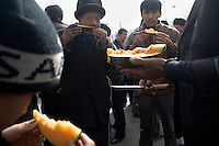 Uighur men eat cantaloupe at a market in Kashgar, Xinjiang, China. Cantaloupe is also known as hami melon or hami gua in Xinjiang.