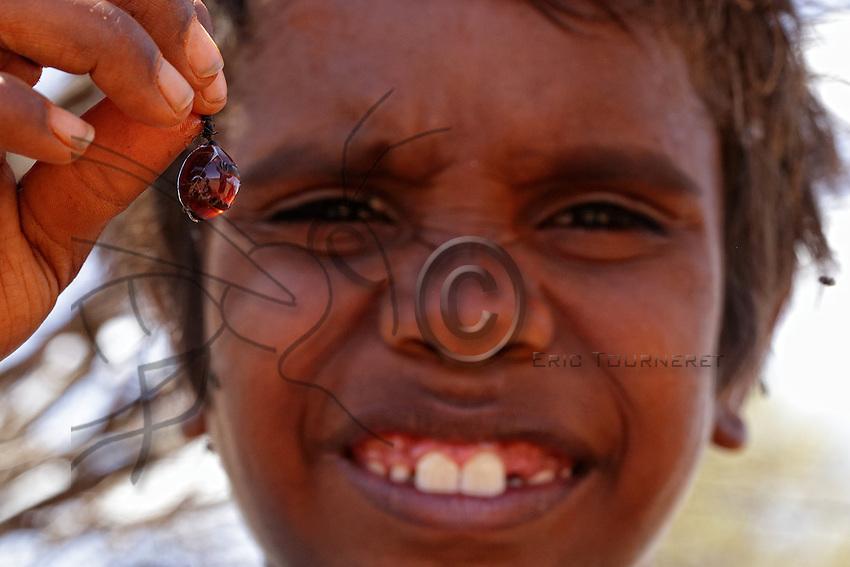 An Aborigine child shows us a honeypot ant.///Un enfant aborigène montre une fourmi pots de miel.