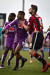 Home defender Ryan Edwards grabs Rueben Reid's neck at a corner as Morecambe (red stripes) hosted Plymouth Argyle in a League 2 fixture at the Globe Arena. The stadium was opened in 2010 and replaced Morecambe's traditional home of Christie Park which had been their home since 1921, the year after their foundation. Plymouth won this fixture by 2-0 watched by 2,081 spectators, in a game delayed by 30 minutes due to traffic congestion affecting travelling Argyle fans.