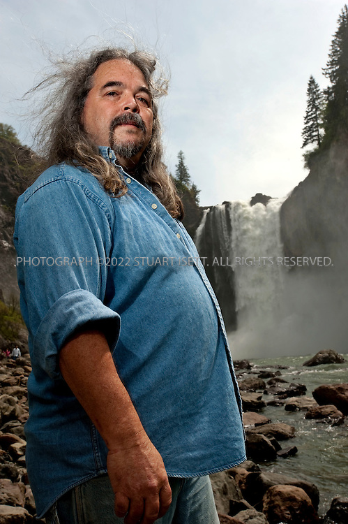 "5/10/2009--Snoqualmie, WA, USA..Ray Mullen, the Snoqualmie tribe's ""drum bearer"" and one of nine members of the democratically elected Tribal Council that runs the tribe, poses at Snoqualmie Falls, what he calls the tribe's 'church'. As drum bearer, Mullen is responsible for learning traditional Snoqualmie songs and sharing them at tribal ceremonies whenever he is called to serve. ..The Snoqualmie Falls is a 268 ft (82 m) waterfall on the Snoqualmie River between Snoqualmie and Fall City, Washington, USA. For the Snoqualmie People, who have lived for centuries in the Snoqualmie Valley in western Washington, Snoqualmie Falls is central to their culture, beliefs, and spirituality. A traditional burial site, to the Snoqualmie, the falls are ""the place where First Woman and First Man were created by Moon the Transformer"" and ""where prayers were carried up to the Creator by great mists that rise from the powerful flow."" The mists rising from the base of the waterfall are said to serve to connect Heaven and Earth...©2009 Stuart Isett. All rights reserved."