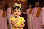 Little girl taking care of by  nuns in a Temple in Mandalay, Myanmar. She's striking few poses away from the nuns.