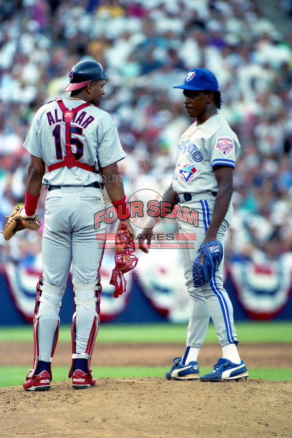 Cleveland Indians catcher Sandy Alomar Jr talks with Toronto Blue Jays pitcher Juan Guzman during the Major League Baseball All-Star Game at Jack Murphy Stadium  in San Diego, California.  (MJA/Four Seam Images)