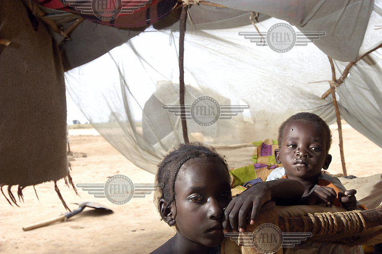 Children in the Bilel camp for internally displaced persons (IDPs). A distribution of plastic sheeting was made by the UNHCR to strengthen shelters as the rainy season began. The residents of the camp fled their homes after being attacked by Janjaweed militias.