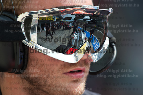 McLaren Formula One driver Jenson Button of Britain is reflected on the visor of a serviceman as he stops in the pit during the free practice session of the Hungarian F1 Grand Prix in Mogyorod (about 20km north-east from Budapest), Hungary. Thursday, 28. July 2011. ATTILA VOLGYI