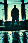 Man standing in empty room with floorboards looking out window