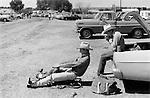 Evanston Wyoming USA 1971. Two young cowboys, preparing for a rodeo in the car park. One sits on a horse saddle that is on the ground and pretends he is on a horse while another lights a cigarette sitting in the trunk of their automobile.